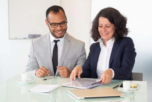 Cheerful business people signing contract. Smiling multiethnic businessman and businesswoman sitting at table and working with papers in office. Paperwork concept